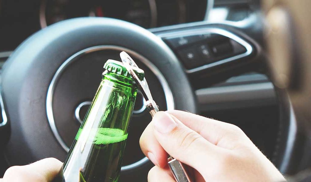 Man opening a beer while in a running car