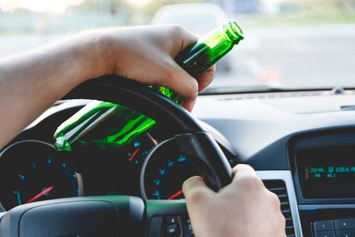 A man driving a car with a bottle of beer in his hand.
