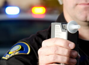 Police officer holding alcotest machine for breath test